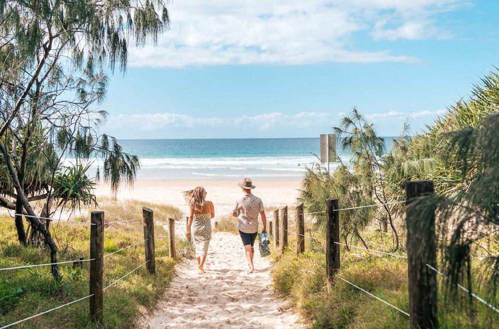 2 people walking through a beach access to Coolum Beach