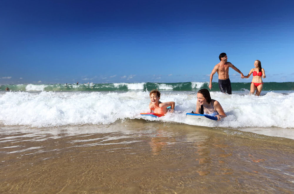 2 children surfing on body boards and their parents are behind them in the ocean