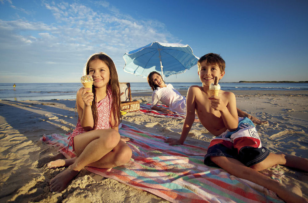 2 children eating icecream on a beach with their mother