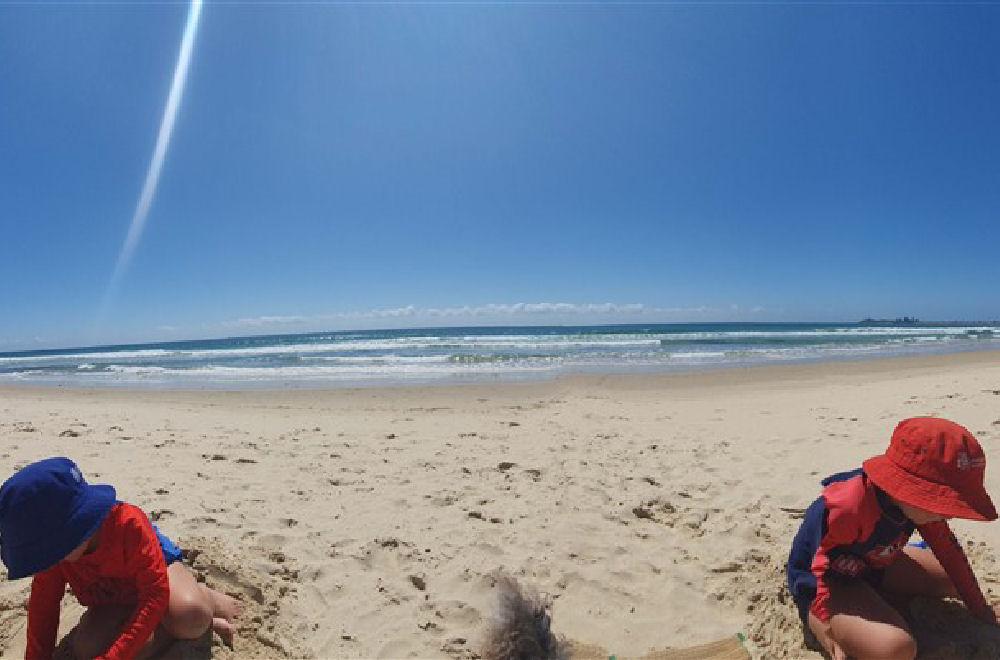 2 boys playing in the sand at Alexandra Headland Beach