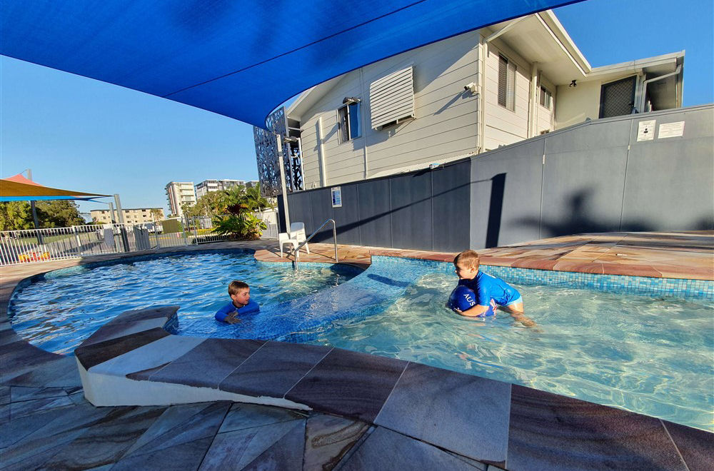 2 boys playing in the heated pool at Alex Beach Cabins