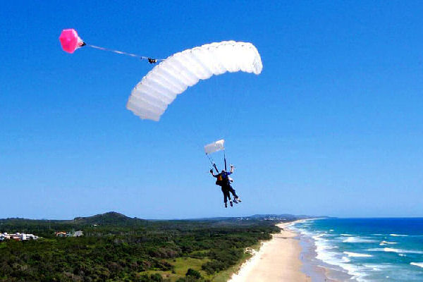 tandem skydivers about to land on a beach in Noosa Sunshine Coast