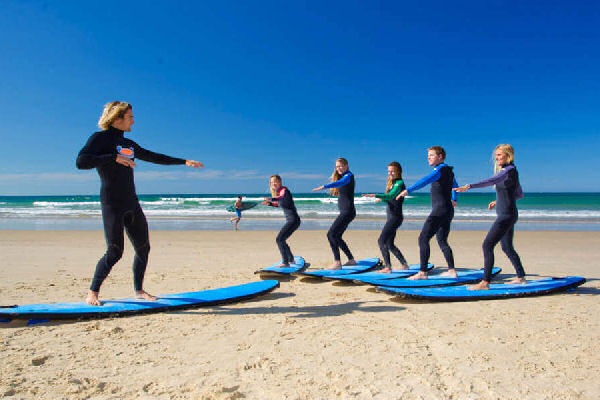 an instructor teaching children how to surf on the sand