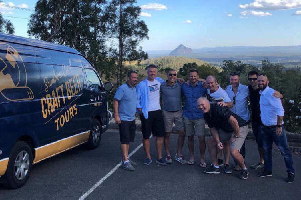 a group of males next to a Sunshine Coast Craft Beer Tours mini van