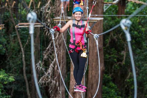 Woman walking on a high ropes course at Treetop Challenge Sunshine Coast